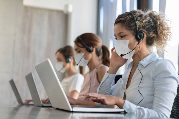 Group of customer service representatives working at a call center wearing facemask stock photo