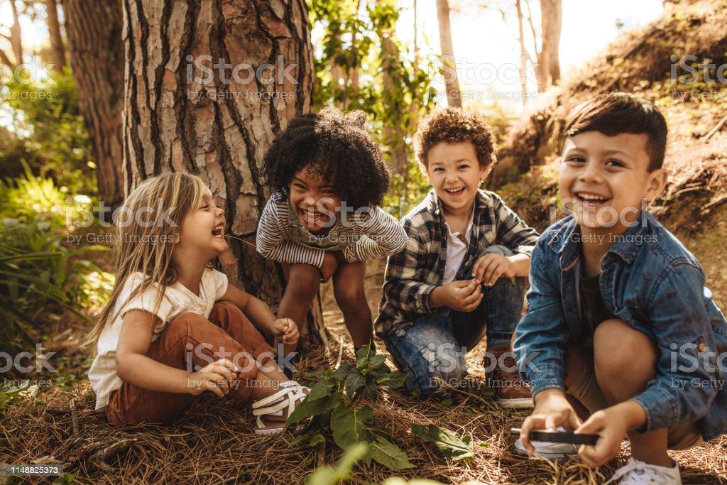 Gruppe von niedlichen Kindern, die im Wald spielen - Lizenzfrei Abenteuer Stock-Foto