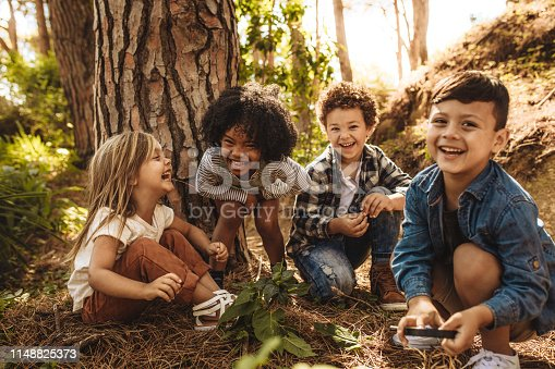 Group of cute kids sitting together in forest and looking at camera. Cute children playing in woods.