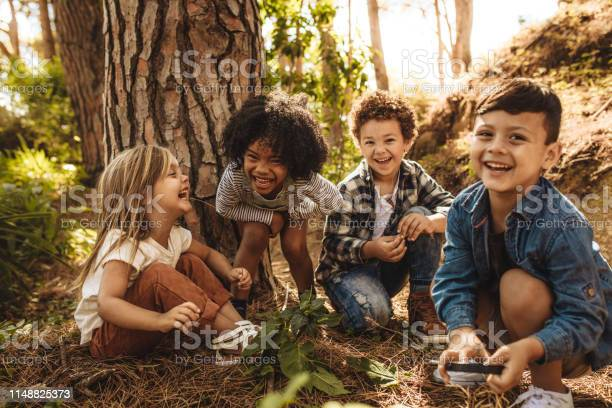 Gruppe Von Niedlichen Kindern Die Im Wald Spielen Stockfoto und mehr Bilder von Abenteuer