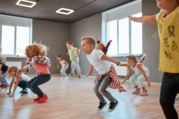Group of cute little boys and girls studying modern dance in studio. Children jumping while having a choreography class Group of cute little boys and girls studying modern dance in studio. Children jumping while having a choreography class. Sport. Active lifestyle dance studio stock pictures, royalty-free photos & images