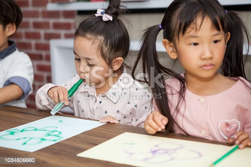 639271192istockphoto group of Cute little girl and boy student blowing color pen painting  together with nursery teacher in classroom school . Happy children in a kindergarten . kid artist multiethnic 1034606660