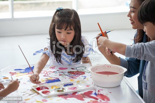 639271192 istock photo group of Cute little girl student painting  together with nursery teacher in classroom school . Happy children in a kindergarten 1034606648