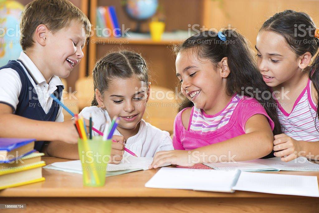 Group of cute schoolchildren having fun in classroom stock photo
