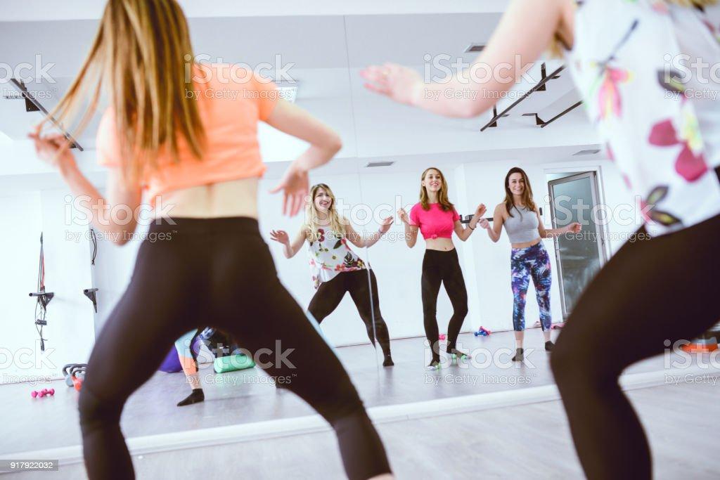 Gruppe von niedlichen Lächeln Frauen Training Zumba vor dem Spiegel im Fitness-Studio – Foto