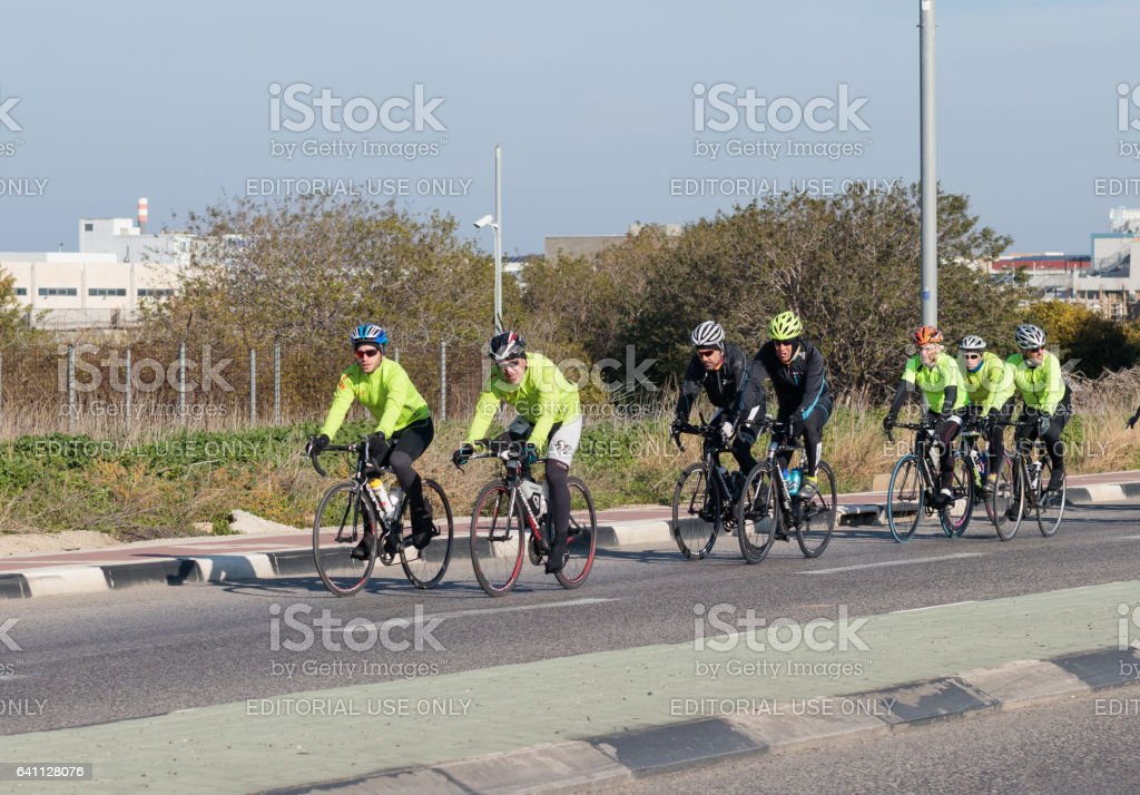 91a87d315 Group of cyclists on winter morning trains on intercity road royalty-free  stock photo