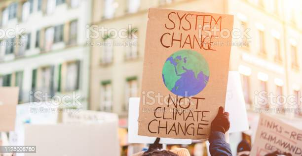 Photo of Group of demonstrators on road, young people fight for climate change - Global warming and enviroment concept - Focus on banner