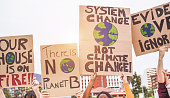 istock Group of demonstrators on road, young people from different culture and race fight for climate change - Global warming and enviroment concept - Focus on banners 1147070895