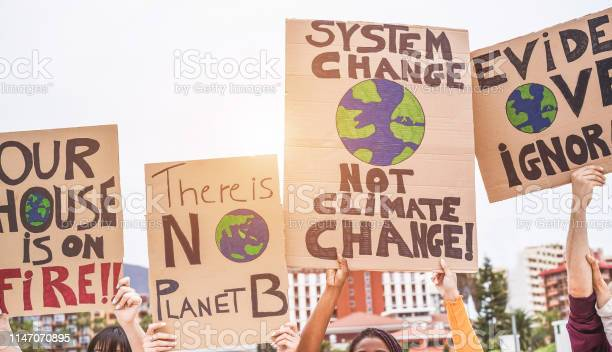 Photo of Group of demonstrators on road, young people from different culture and race fight for climate change - Global warming and enviroment concept - Focus on banners