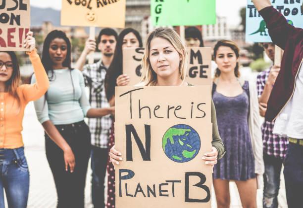 道路上的一群示威者, 來自不同文化和種族的年輕人為氣候變化而戰--全球變暖和環境概念--關注金髮碧眼的女孩臉 - 氣候 個照片及圖片檔
