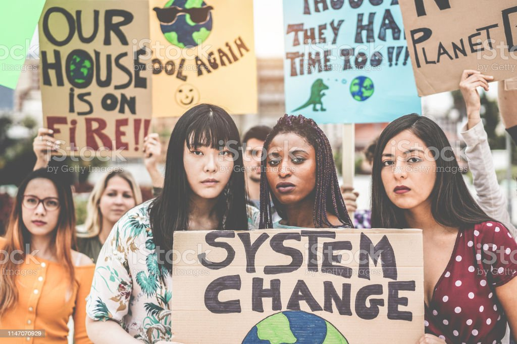 Group of demonstrators on road, young people from different culture and race fight for climate change - Global warming and enviroment concept - Main focus on afro girl face royalty-free stock photo