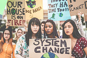 Group of demonstrators on road, young people from different culture and race fight for climate change - Global warming and enviroment concept - Main focus on afro girl face