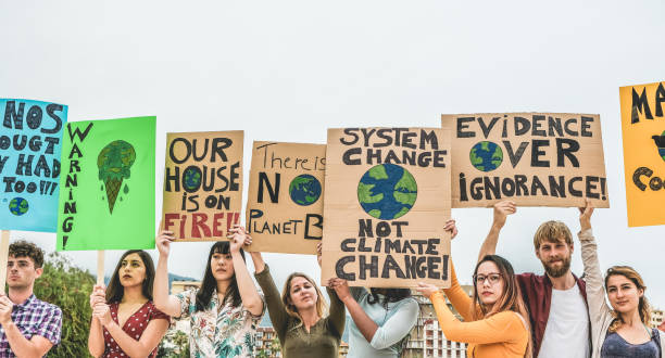 Group of demonstrators on road, young people from different culture and race fight for climate change - Global warming and enviroment concept - Focus on banners stock photo