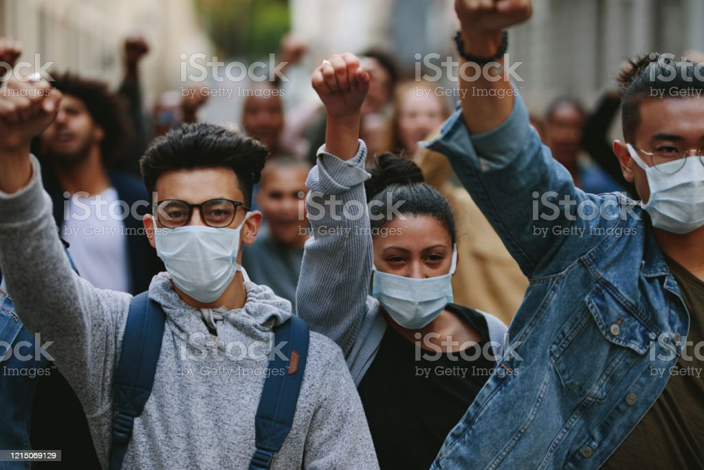 Group of demonstrators protesting in the city Group of people wearing face mask protesting and giving slogans in a rally. Group of demonstrators protesting in the city. Activist Stock Photo