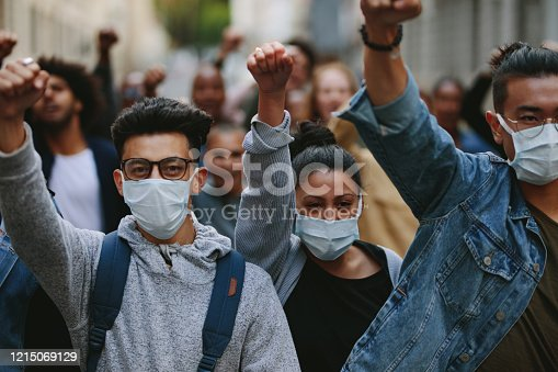 Group of people wearing face mask protesting and giving slogans in a rally. Group of demonstrators protesting in the city.