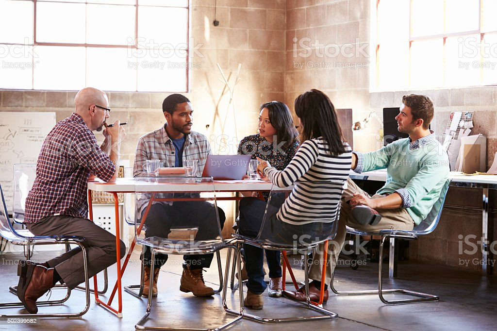Group Of Designers Having Meeting Around Table In Office stock photo