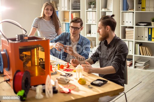 886646936 istock photo Group of Designers Using 3D Printer 886646940