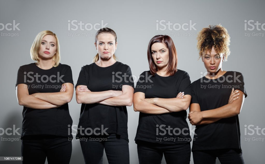Group of determinated women protesting Group of displeased women wearing black clothes, standing with arms crossed against grey background and staring at camera. Studio shot. Activist Stock Photo