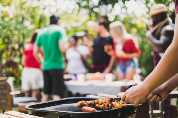 grupa deversity ludzi o grilla / grilla w domu, gotowanie grillowanego mięsa / wołowiny na lunch, szczęśliwy przyjaciele strony koncepcji stylu życia - barbecue zdjęcia i obrazy z banku zdjęć