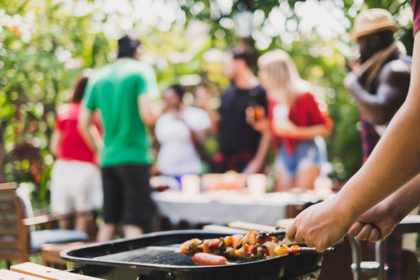 Group of deversity people having barbecue/barbeque party at home, cooking grilled meat/beef for lunch, happy friends party lifestyle concept stock photo