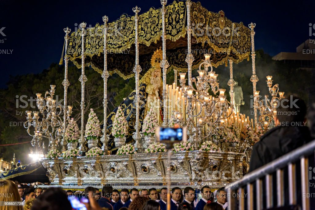 A group of devote men carry a religious float during Holy Week procession in Malaga. stock photo