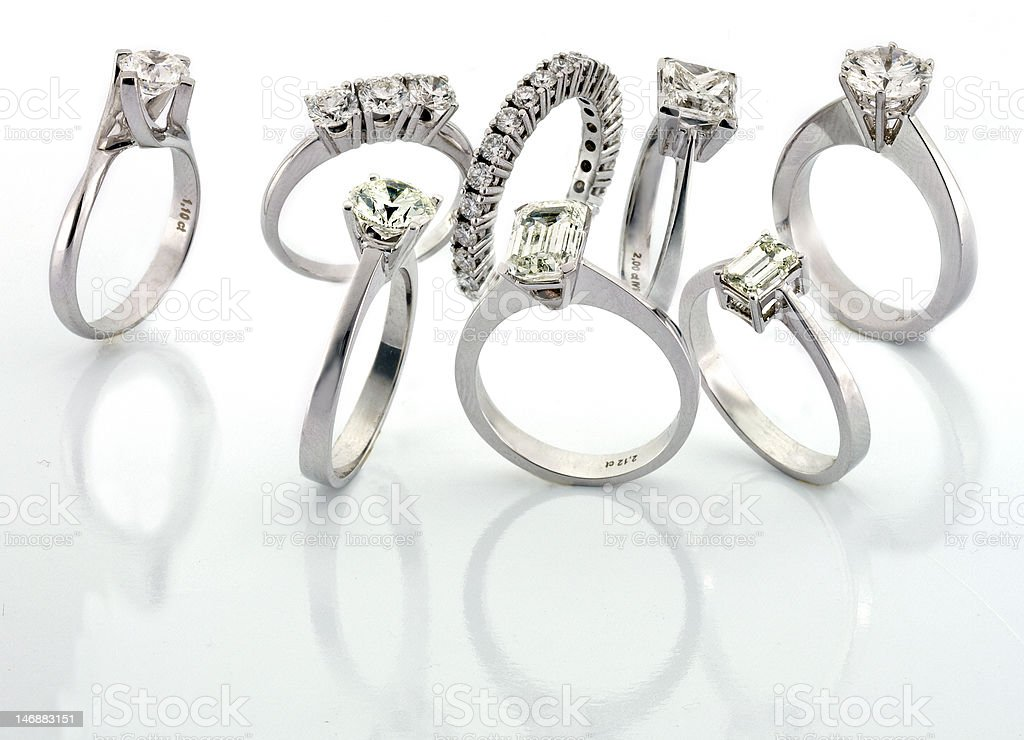 Group of diamond rings on reflective surface. stock photo