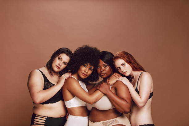 Group of different size women in lingerie Group of different size women in lingerie looking at camera with proud. Multiracial women in different under garments posing together. body positive stock pictures, royalty-free photos & images