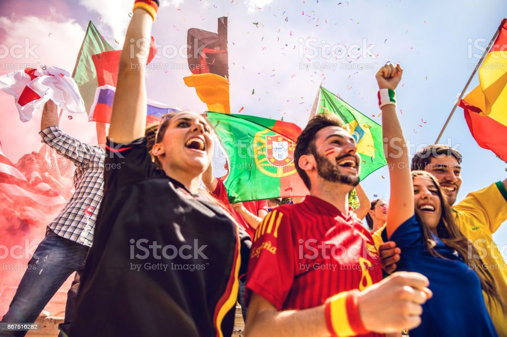 Group of different team fans together at stadium during a football league stock photo