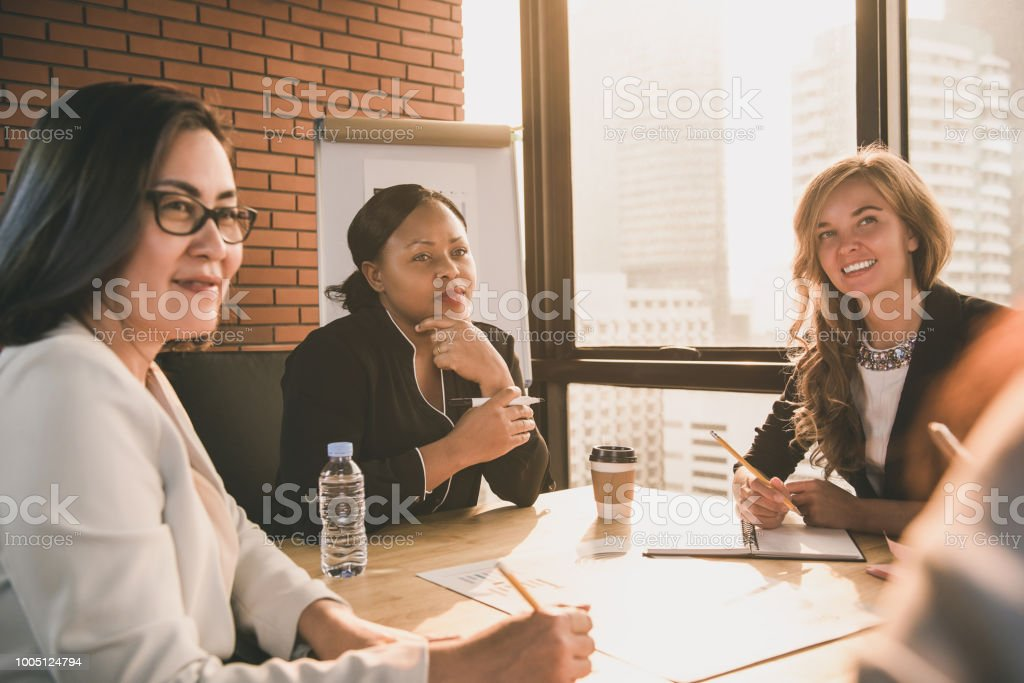Group of diverse businesswoman leaders listening to presentation in...