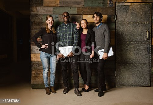 istock Group of diverse colleagues standing in an office 472347684