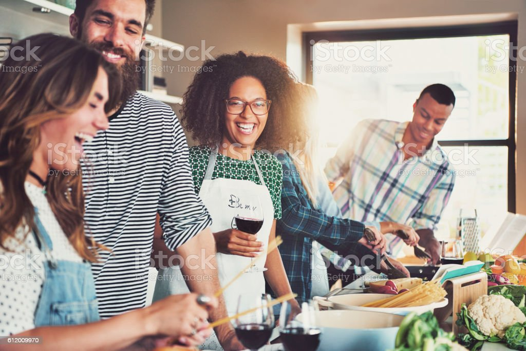 Group of diverse friends drinking and cooking stock photo