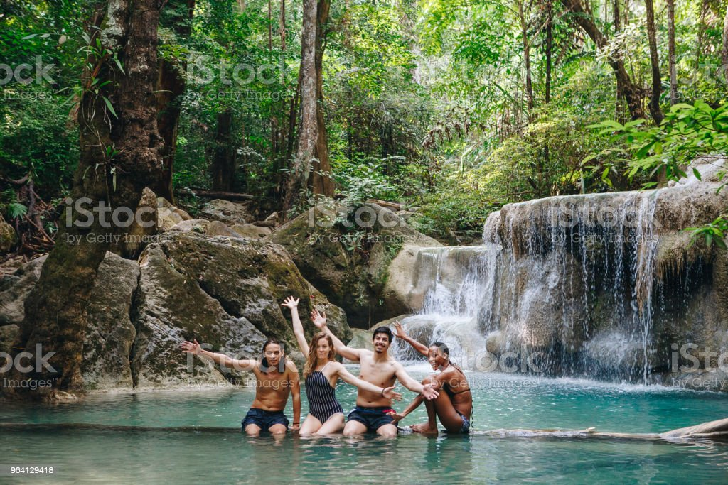 Group of diverse friends enjoying the waterfall stock photo