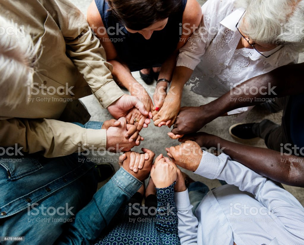 Group of diverse hands holding each other support together teamwork aerial view royalty-free stock photo