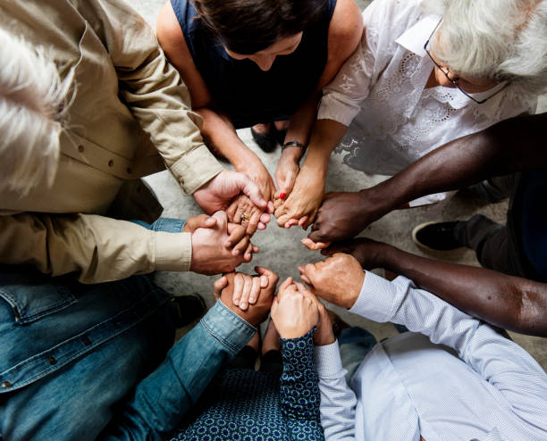 Group of diverse hands holding each other support together teamwork aerial view stock photo