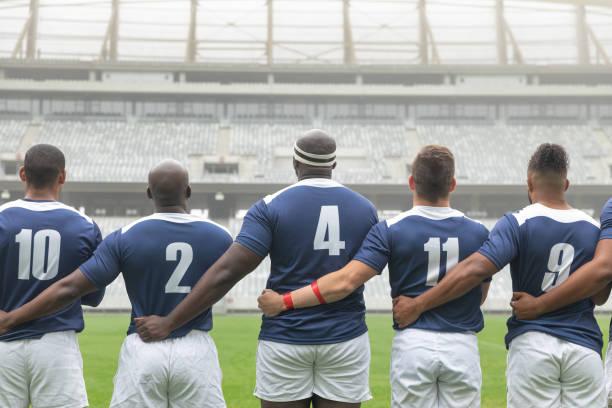 groupe de joueurs de rugby masculins divers prenant l'engagement ensemble dans le stade - photos de rugby photos et images de collection