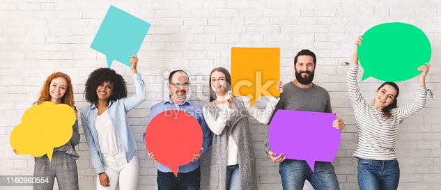 Global communications. Group of happy young diverse people holding empty colorful speech bubbles and smiling at camera