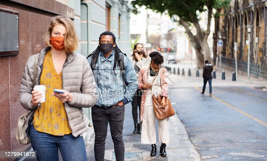 Diverse group of people wearing protective face masks practicing social distancing while waiting in a line on a city sidewalk