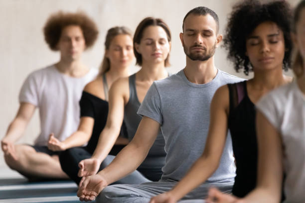 Group of diverse people meditating visualizing during yoga session stock photo