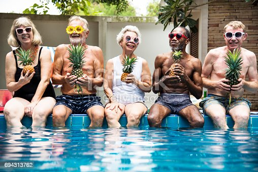 istock Group of diverse senior adults sitting at poolside holding pineapples together 694313762