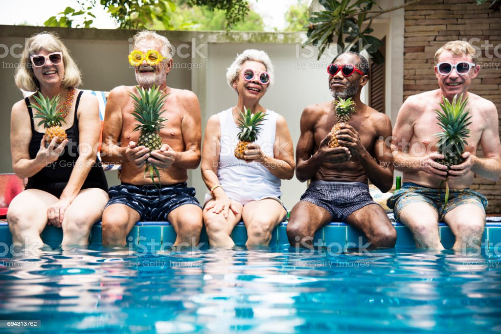Group of diverse senior adults sitting at poolside holding pineapples together stock photo
