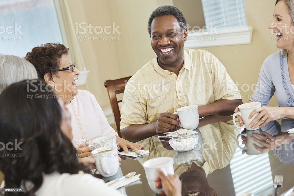 Group of diverse senior friends laughing together over coffee royalty-free stock photo