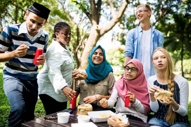 多様な学生のグループは一緒に昼食をとっています。 - religion culture ストックフォトと画像