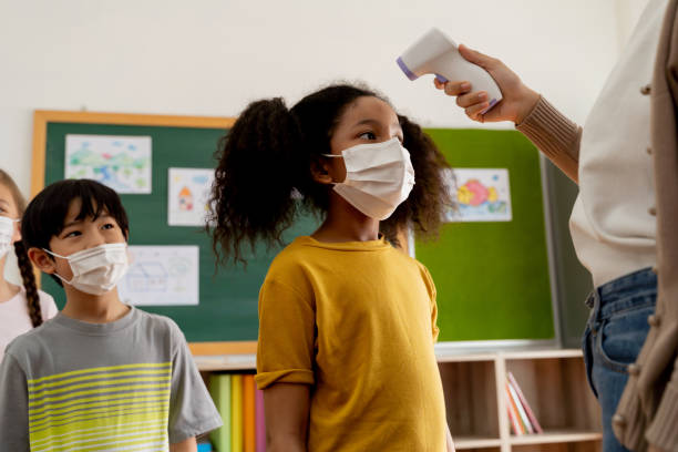 Group of diverse students in school building checked and scanned for temperature check. Elementary pupils are wearing a face mask and line up before entering into classroom. stock photo