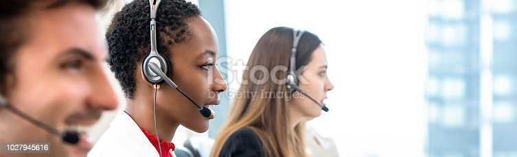 istock Group of diverse telemarketing team in call center office banner background 1027945616