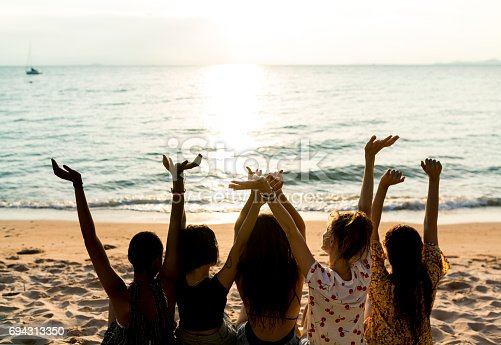 istock Group of diverse women sitting at the beach together 694313350