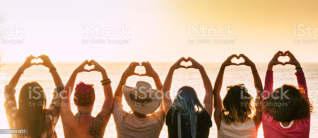 Group of diversity alternative young woman enjoying the sunset at the sea doing hearth symbol with hands - people enjoying friendly lifestyle - vacation in friendship concept for females Group of diversity alternative young woman enjoying the sunset at the sea doing hearth symbol with hands - people enjoying friendly lifestyle - vacation in friendship concept for females Activity Stock Photo