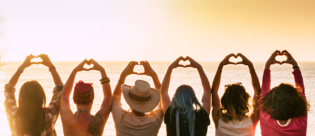 Group of diversity alternative young woman enjoying the sunset at the sea doing hearth symbol with hands - people enjoying friendly lifestyle - vacation in friendship concept for females stock photo