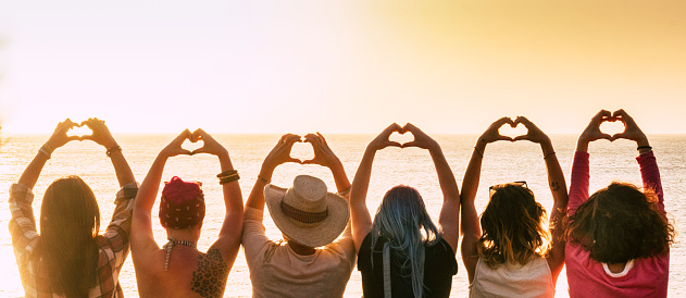 Group Of Diversity Alternative Young Woman Enjoying The Sunset At The Sea Doing Hearth Symbol With Hands People Enjoying Friendly Lifestyle Vacation In Friendship Concept For Females Stock Photo - Download Image Now