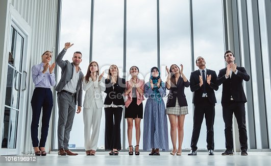istock Group of diversity business people celebrating clapping hands for teamwork and successful 1016196912