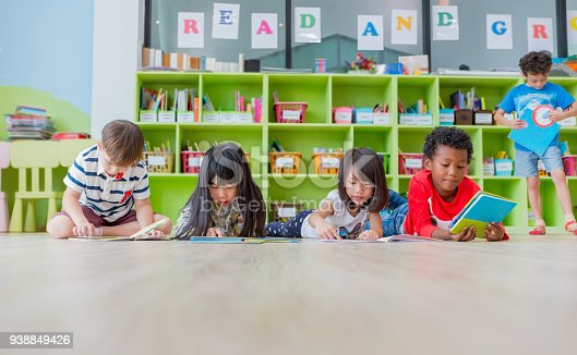istock Group of diversity kid lay down on floor and reading tale book in preschool library,Kindergarten school education concept 938849426